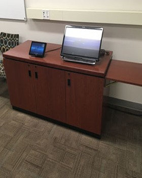 AV control equipment racks in a credenza with drop-shelf and cable access for a touch panel and monitor.